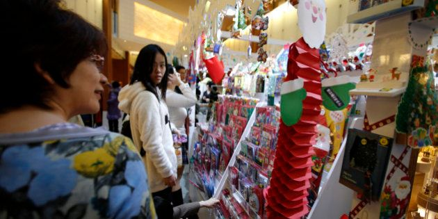 People look at Christmas cards displayed for sale at a stall in a shopping mall in Tokyo, Japan, on Thursday,...