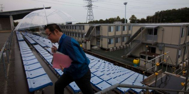 A employee of the Tokyo Electric Power Co. walks up stairs near temporary housing built for workers who...