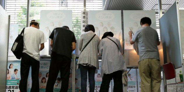 Voters fill out their ballots for the Japanese parliament's upper house election at a polling station...