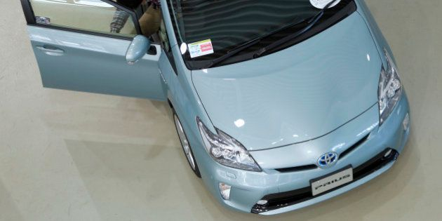 A visitor examines a Toyota Motor Corp. Prius vehicle displayed at the company's showroom in Tokyo, Japan,...