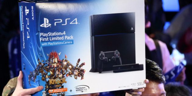 The first customer to purchase the PlayStation 4 (PS4) video game console, left, holds up the box as...