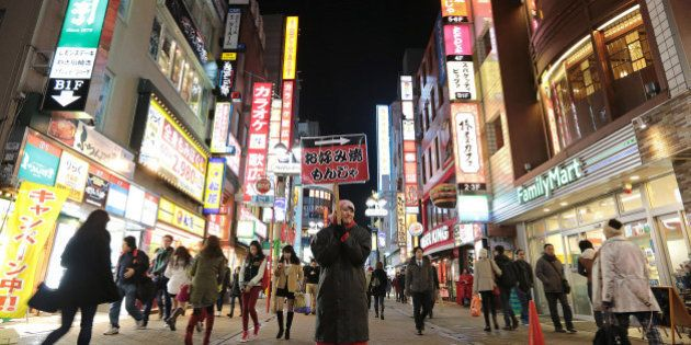 An employee holds a sign for a 'okonomiyaki' restaurant at night in the Shibuya district of Tokyo, Japan,...
