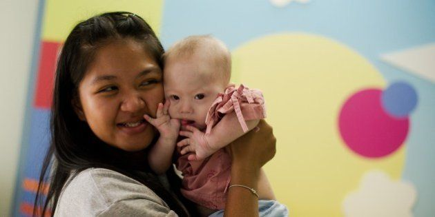 Thai surrogate mother Pattaramon Chanbua (L) holds her baby Gammy, born with Down Syndrome, at the Samitivej...