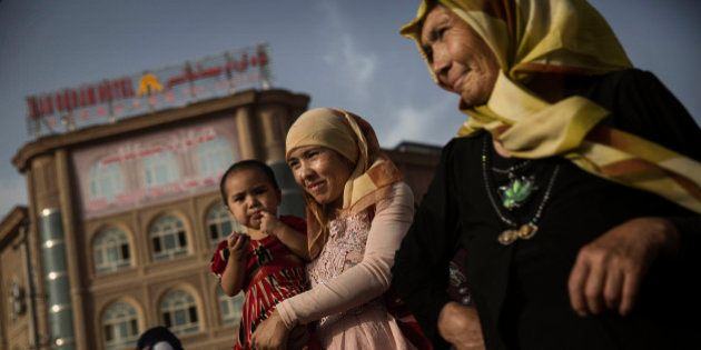 KASHGAR, CHINA - AUGUST 01: A Uyghur woman walks with her baby at a market on August 1, 2014 in old Kashgar,...