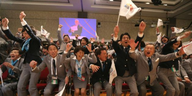 Japanese Prime Minister Shinzo Abe (3-R) celebrates alongside Tokyo 2020 delegation members after IOC...