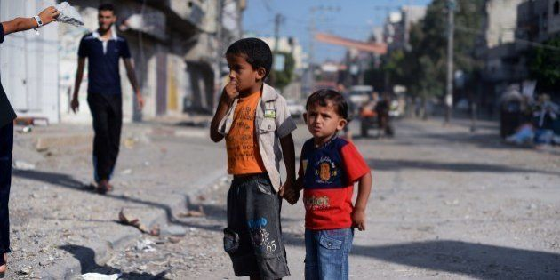 Two Palestinian boys hold hands as they look at the bombed out remains of a mosque that was targeted...
