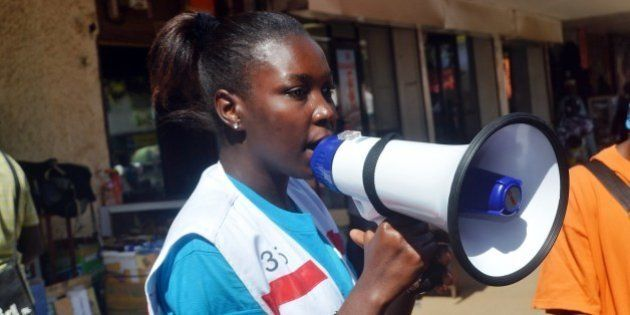 A member of the Guinean Red Cross uses a megaphone to give information concerning the Ebola virus during...