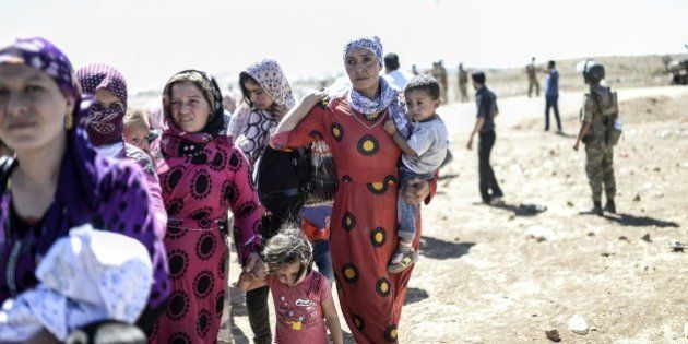 Syrian Kurd families carry their belongings after they crossed the border between Syria and Turkey near...