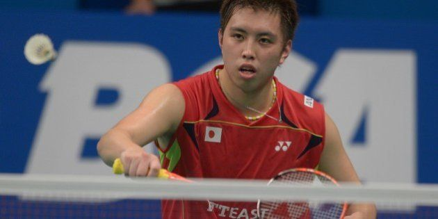 Kenichi Tago of Japan hits a return against Lee Chong Wei of Malaysia at the badminton 2014 Indonesia...
