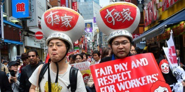 Labour union members wearing gear of Sukiya fast-food beef-bowl restaurant hold placards to demand payment...