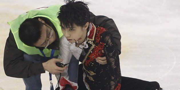 Medical personnel tend to Japanese skater Yuzuru Hanyu (R) on the ice rink after he crashed into Yan...