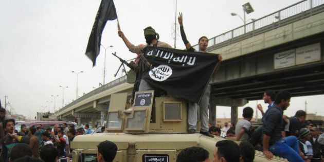 FILE - in this Sunday, March 30, 2014, file photo, Islamic State group militants hold up their flag as...