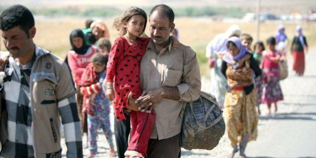 A displaced Iraqi man from the Yazidi community carries his daughter as they cross the Iraqi-Syrian border...