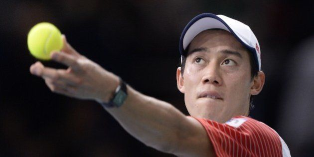 Japan's Kei Nishikori serves the ball to Serbia's Novak Djokovic during the semi-finals of the ATP World...
