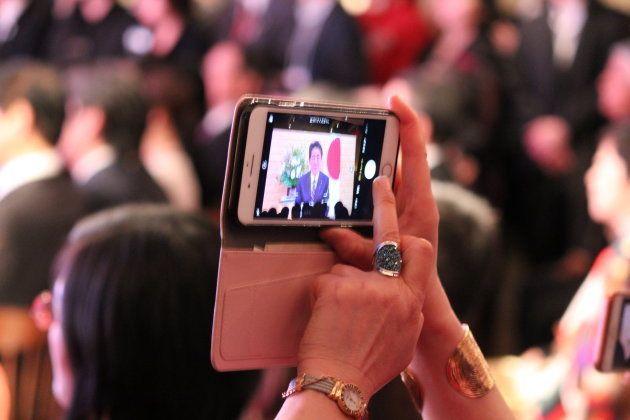 安倍総理のビデオメッセージにカメラを向ける参加者