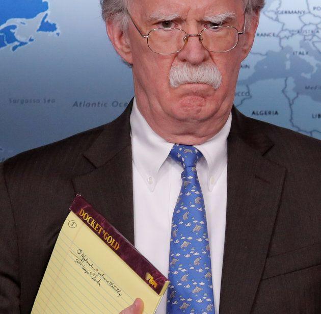 「兵士5000人をコロンビアへ」と走り書きされたノートを持つボルトン大統領補佐官=1月28日、ワシントン