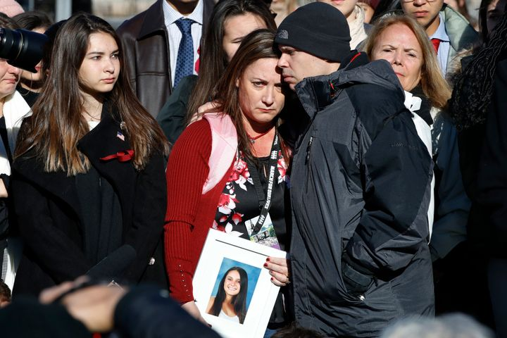 Lori Alhadeff, center, is comforted by her husband Ilan Alhadeff, as she holds a photograph of their daughter, Alyssa Alhadef