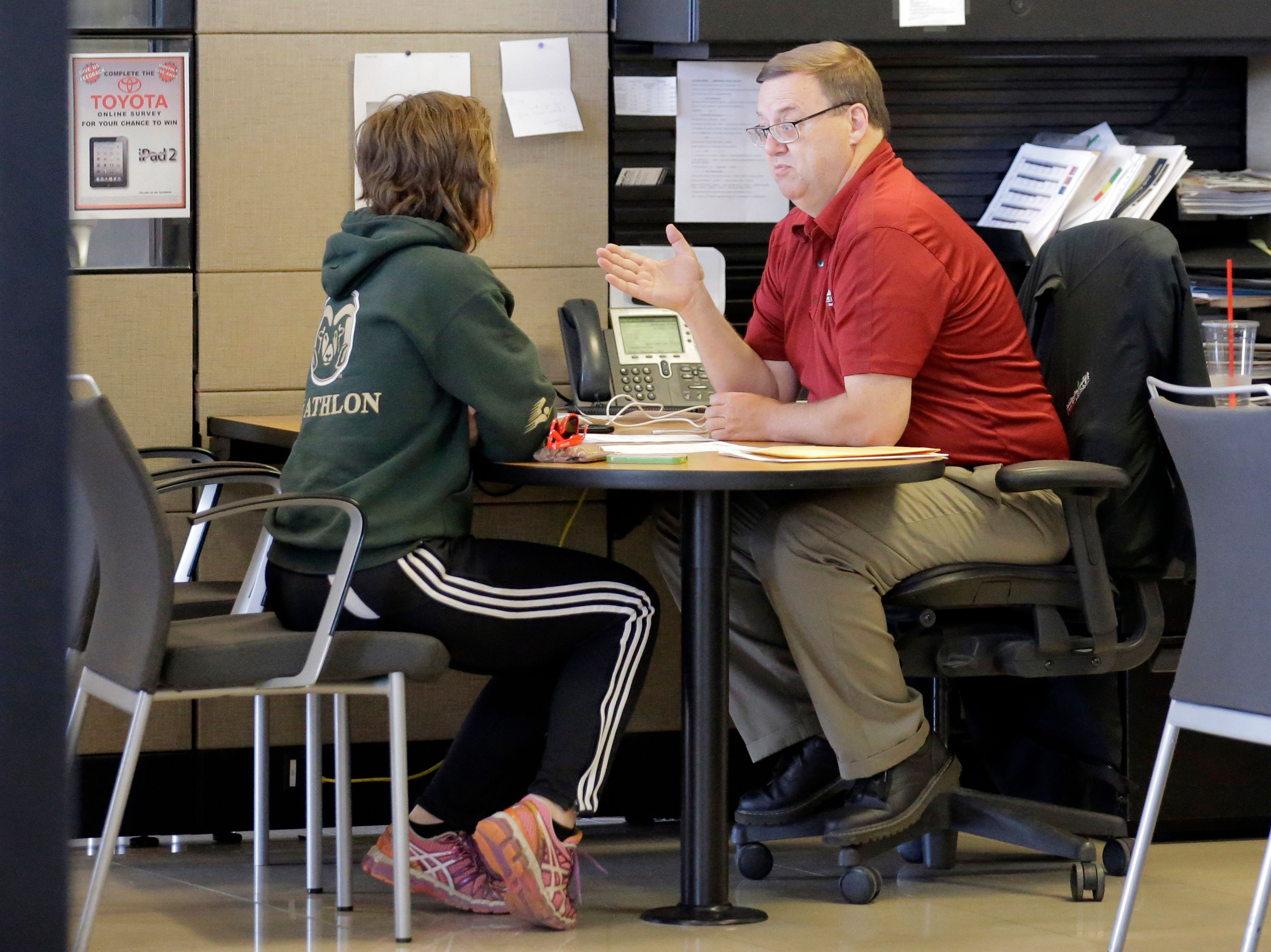 Vehicle shopper Mary Jean Jones speaks with Mark Miller Toyota salesman Doug Lund Tuesday, June 13, 2017, in Salt Lake City. (AP Photo/Rick Bowmer)