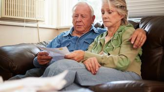 Worried Senior Couple Sitting On Sofa Looking At Bills With Arm Around Wife