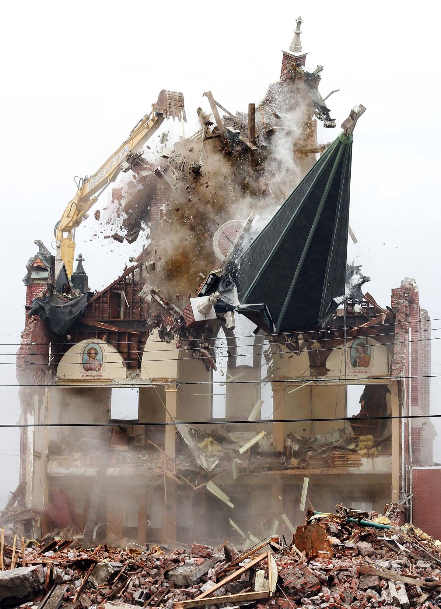 In this Monday, Feb. 11, 2019 photo, the steeple of Saint Joseph's Church in Nanticoke, Pa., is knocked down as Brdaric Excavating began the demolition of the property. The church and an adjoining rectory closed in May 2010 as part of the Catholic church consolidation.