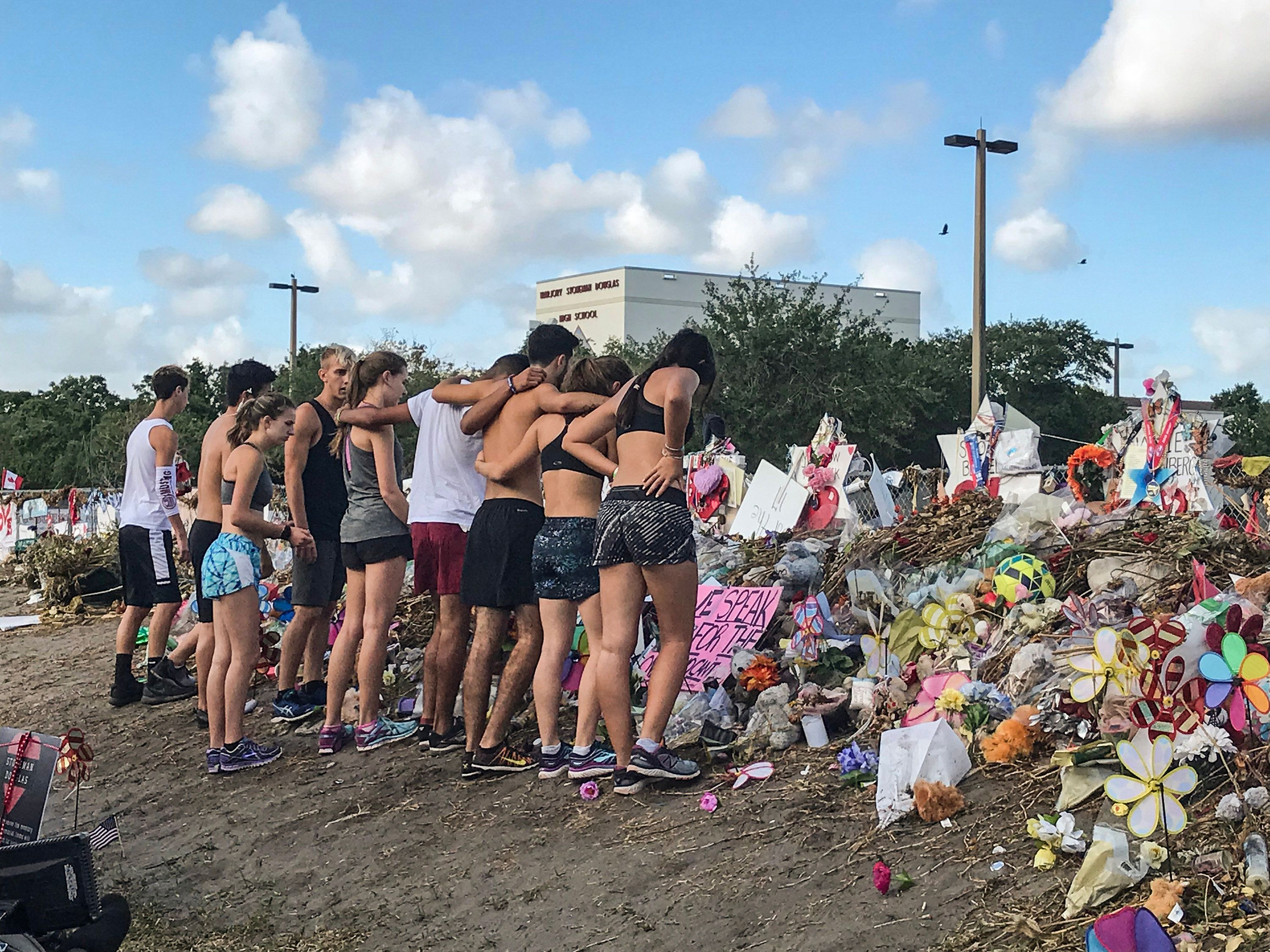 Students from Marjory Stoneman Douglas High School's cross country team stop by the makeshift memorials in front of the school on March 28, 2018. (Phillip Valys/Sun Sentinel/TNS via Getty Images)