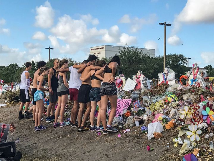 Students from Marjory Stoneman Douglas High School's cross country team stop by the makeshift memorials in front of the schoo