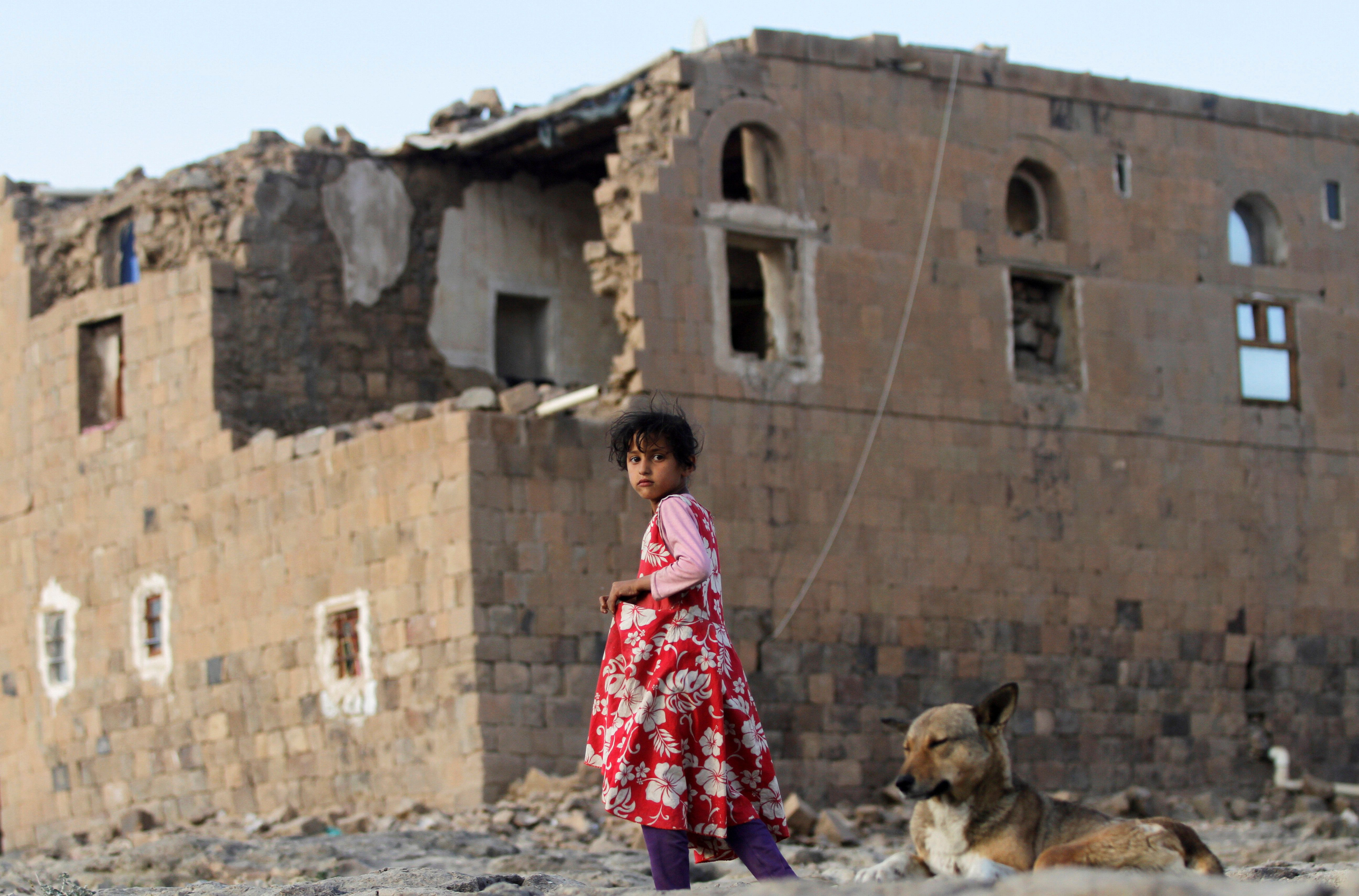 A girl walks near her house destroyed in an airstrike carried out by the Saudi-led coalition in Faj Attan village, Sanaa, Yem