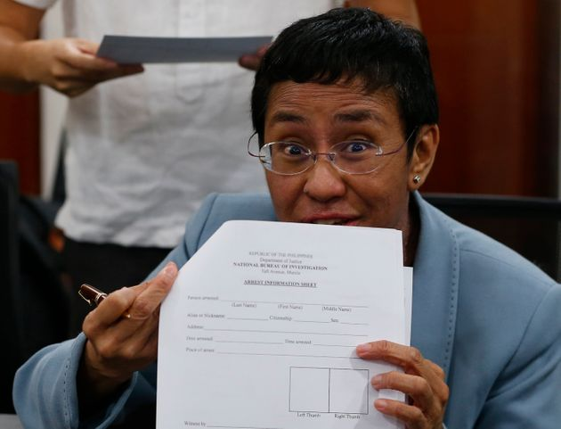 Maria Ressa shows an arrest form after being arrested by National Bureau of Investigation agents in a...