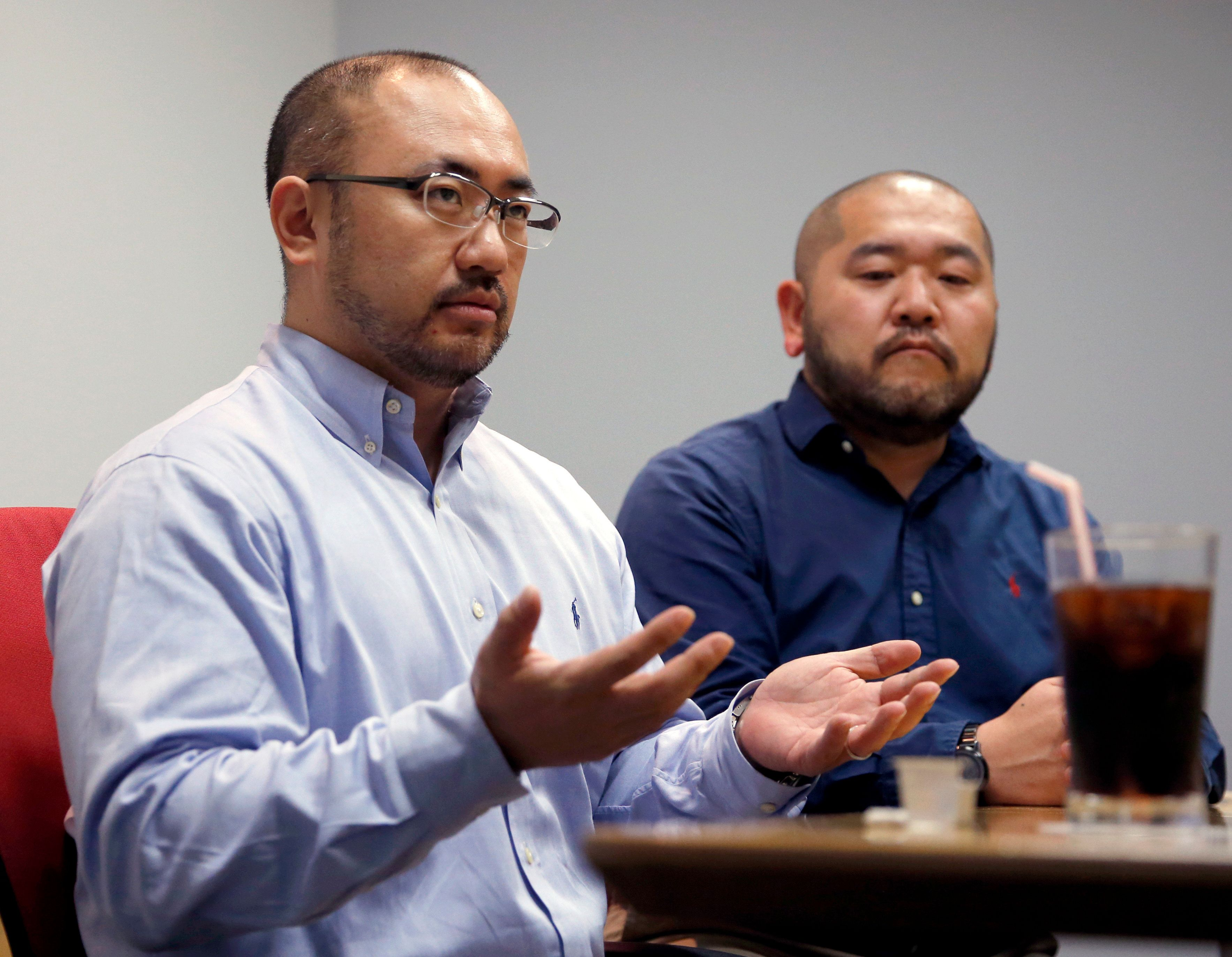 In this Jan. 28, 2019, photo, Kenji Aiba, left, speaks as his partner Ken Kozumi listens during an interview with The Associated Press in Tokyo. Kozumi and Aiba have held onto a marriage certificate they signed at their wedding party in 2013, anticipating that Japan would emulate other advanced nations and legalize same-sex unions. That day has yet to come, and legally they are just friends even though they've lived as a married couple for more than five years. On Thursday, Feb. 14, 2019, Valentine's Day, the couple is joining a dozen other same-sex couples in Japan's first lawsuits challenging the constitutionality of the country's rejection of same-sex marriage. (AP Photo/Toru Takahashi)
