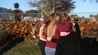 PARKLAND, FLORIDA - FEBRUARY 14:   Sophia Rothenberg and her sister, Emma Rothenberg  (L-R) hug their mother Cheryl Rothenberg while looking on at a memorial setup for those killed at Marjory Stoneman Douglas High School on February 14, 2019 in Parkland,  Florida. Emma and Sophia are students at Marjory Stoneman Douglas High school where a year ago on Feb. 14th, 14 students and three staff members  were killed during the mass shooting. (Photo by Joe Raedle/Getty Images)