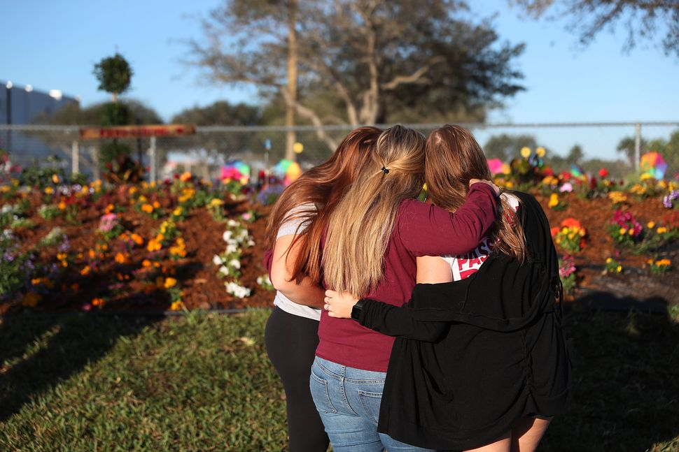 Sophia Rothenberg (L) and her sister, Emma Rothenberg (C), hug their mother Cheryl Rothenberg (R) while looking at a memorial
