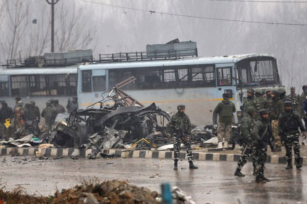 Security forces near the damaged vehicles at Lethpora on the Jammu-Srinagar highway, on February 14,...