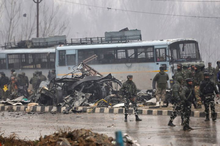 Security forces near the damaged vehicles at Lethpora on the Jammu-Srinagar highway, on February 14, 2019 in Srinagar.