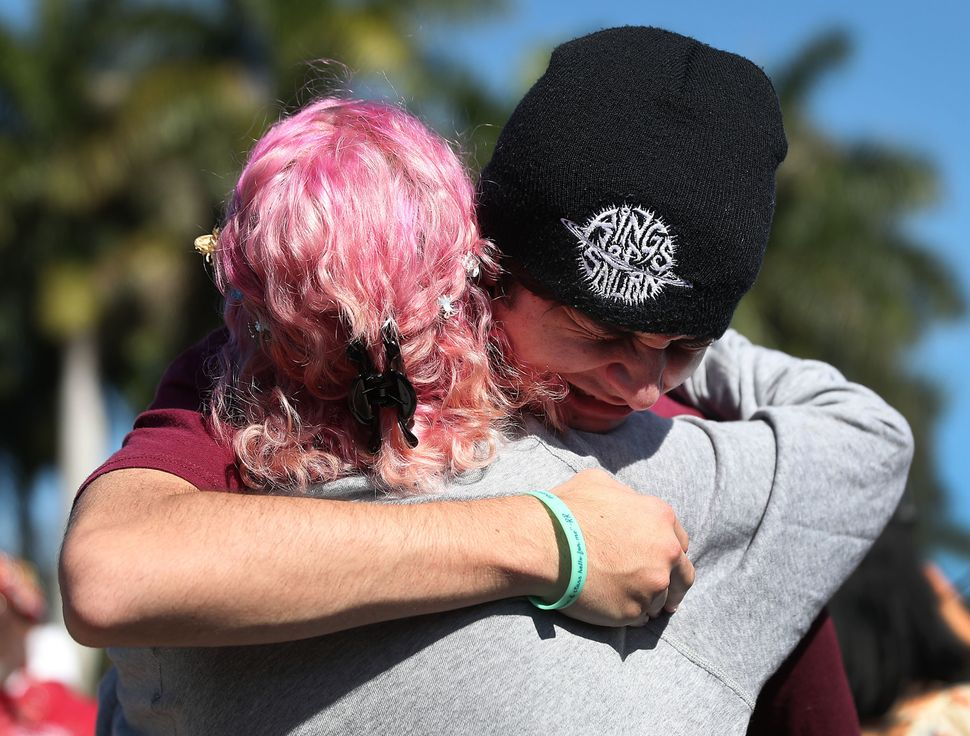 Victoria Gonzalez and Liam Kiernan (L-R), both of whom are students at Marjory Stoneman Douglas High School, comfort each oth