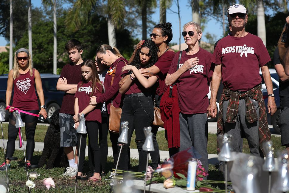 People pause for a moment of silence at 10:17am near Marjory Stoneman Douglas High School.