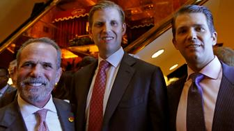 FILE - In this June 5, 2017 file photo, Eric Danziger, CEO of Trump Hotels, left, joins Eric Trump, center, and Donald Trump Jr., both of whom are executive vice presidents of the Trump Organization, as the trio poses for a photograph during an event for Scion Hotels n New York. On Thursday, Feb. 14, 2019, the Trump Organization announced that it will no longer try to open hotels under its Scion and American Idea brands which would have been marketed to budget and mid-priced travelers. (AP Photo/Kathy Willens, File)