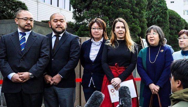 提訴を前に報道陣の取材に応じる原告ら=2月14日、東京地裁前