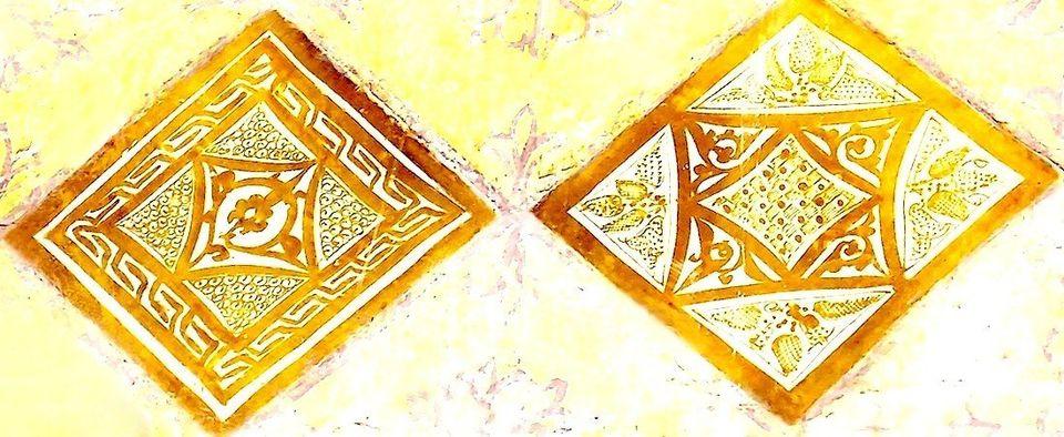 Gros plan sur deux carreaux de céramique lustrée à reflets métalliques dorés....