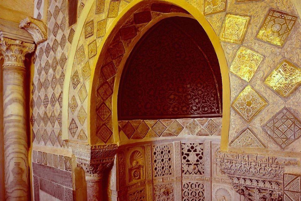 Vue partielle des carreaux lustrés, posés sur la pointe, ornant l'arc du mihrab et la partie...