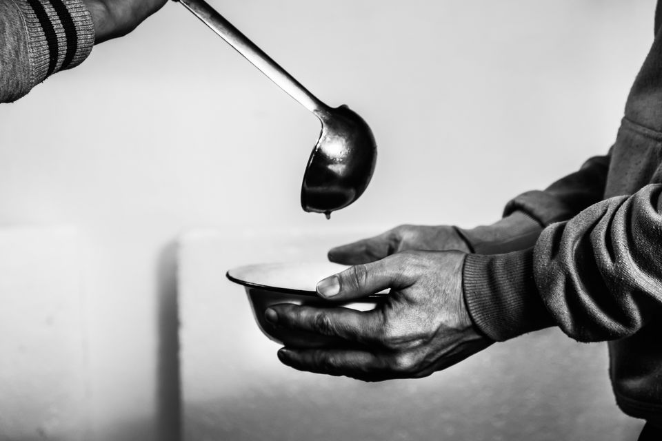 Volunteers feed the homeless. Free soup in a bowl of beggar and ladle.