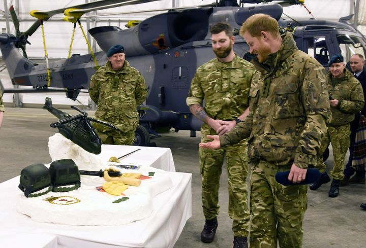 Harry checking out the cake made by British and Norwegian troops.