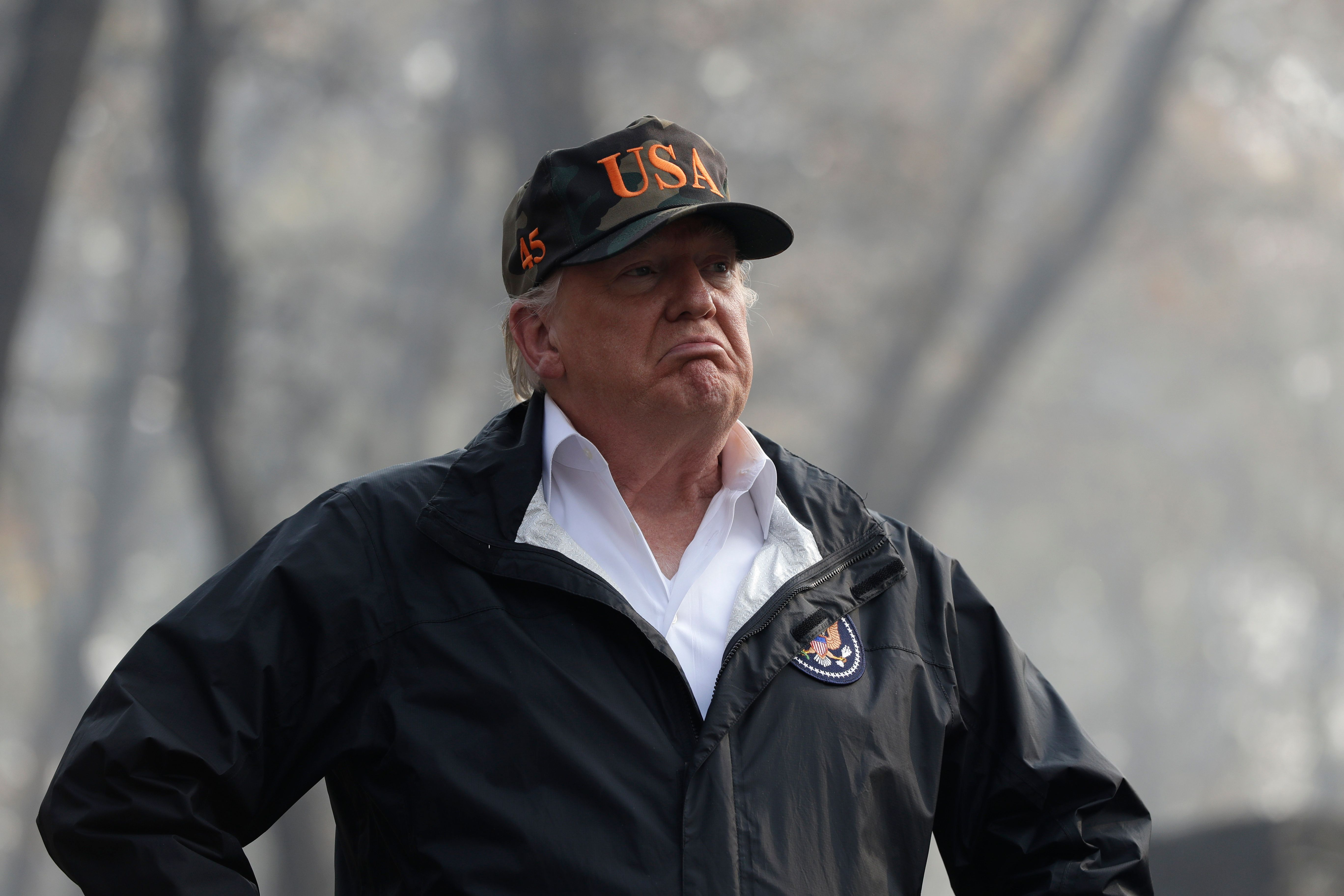 FILE - In this Nov. 17, 2018 file photo U.S. President Donald Trump visits a neighborhood impacted by the wildfires in Paradise, Calif. Forest fires from California to Greece, droughts in Germany and Australia, tropical cyclones Mangkhut in the Pacific and Michael in the Atlantic: scientists say this year's extreme weather offers a glimpse of disasters to come if global warming continues unabated. (AP Photo/Evan Vucci, file)