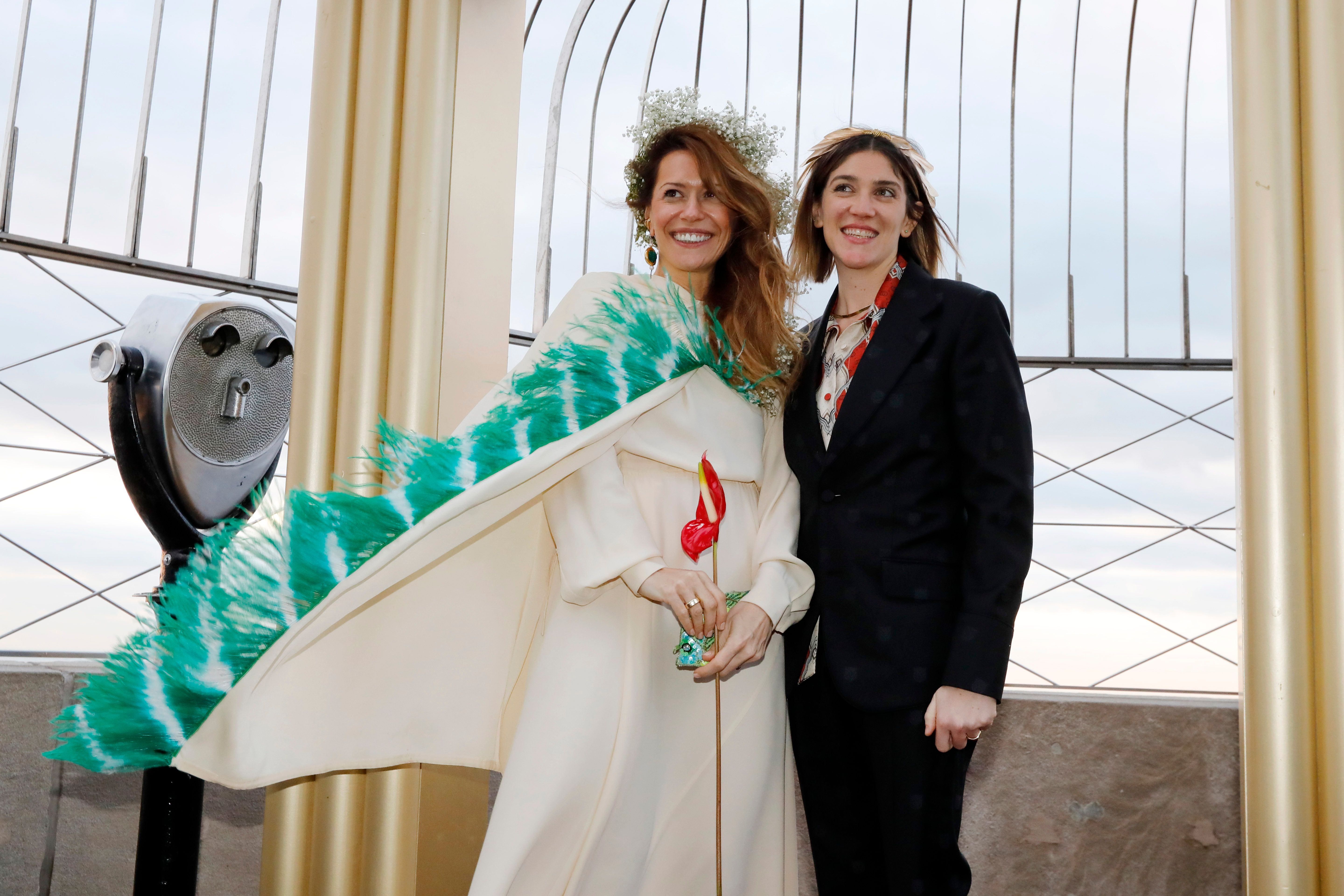Helena Barquet, left, and Fabiana Faria, from New York, pose for photos after their Valentine's Day wedding on the Observation Deck of the Empire State Building, in New York, Thursday, Feb. 14, 2019. (AP Photo/Richard Drew)