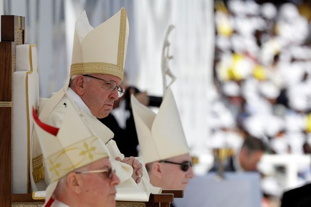 Pope Francis sits in front of the altar as he celebrates a mass at the Sheikh Zayed Sports City Stadium...