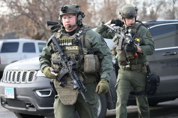 Police officers armed with rifles stage near a commercial building where an active shooter was reported in the 600 block of A