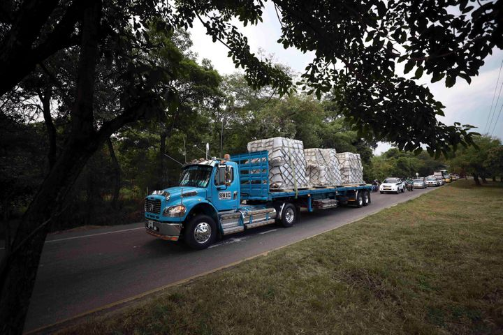 Trucks loaded with USAID humanitarian aid for Venezuela are escorted by police as they arrive at the Tienditas International
