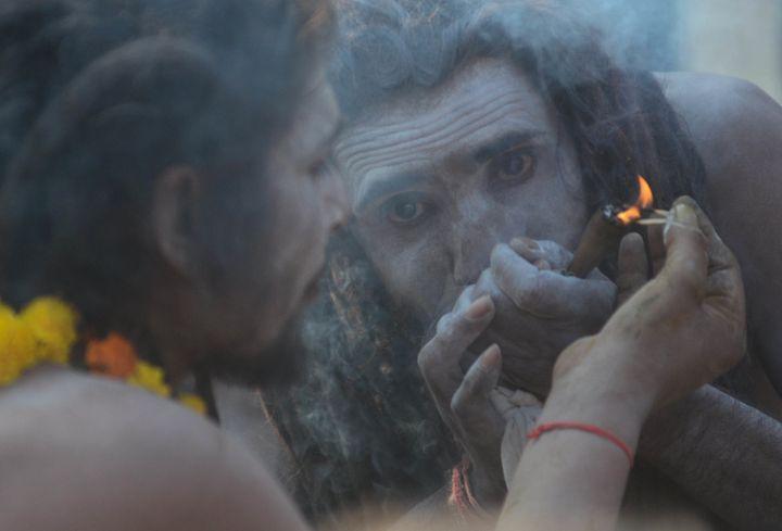 A sadhu of Juna Akhara smokes marijuana in Allahabad on December 25, 2018 .