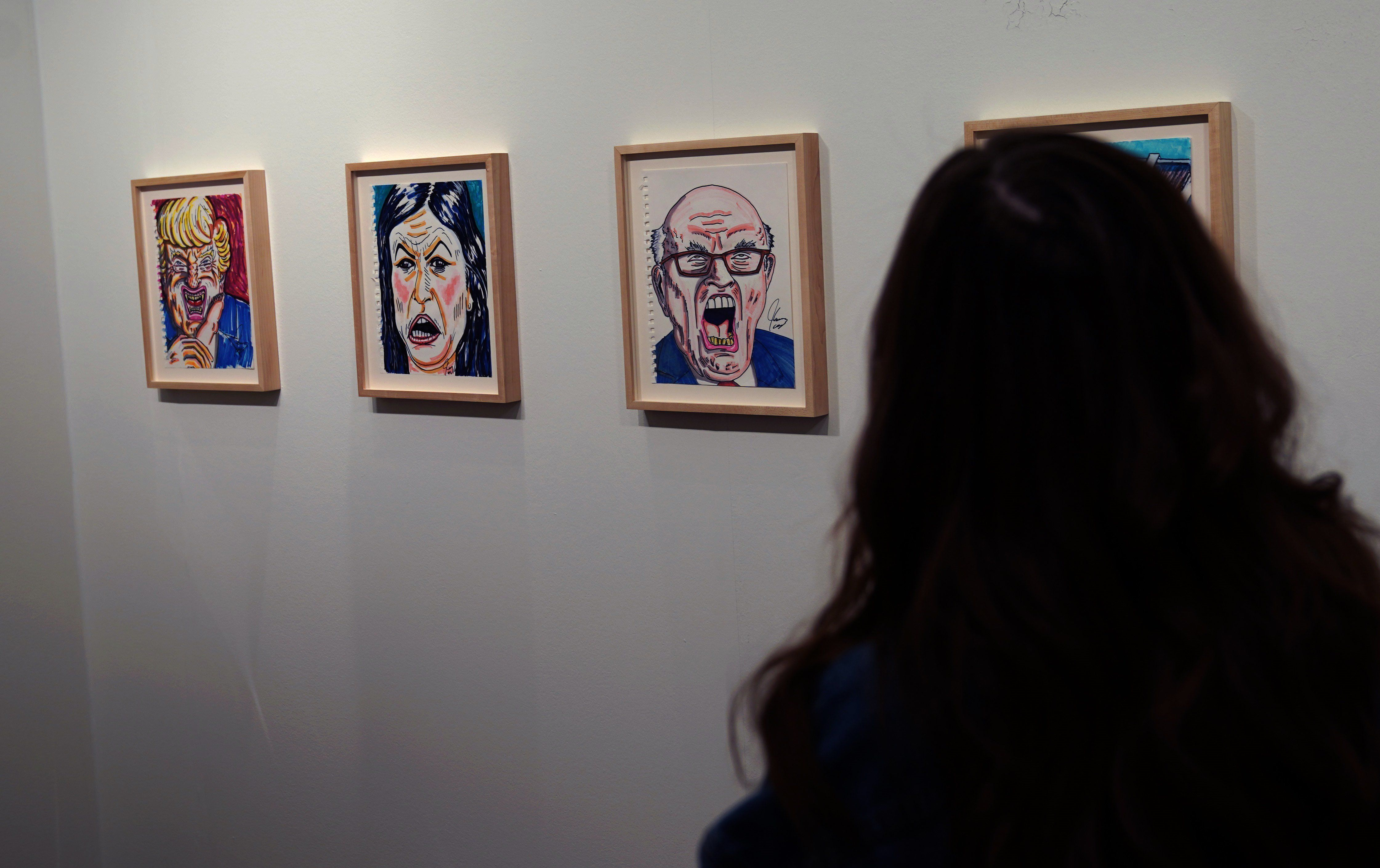People view the artwork of actor and political cartoonist Jim Carrey during the Outsider Art Fair January 17, 2019 at the Metropolitan Pavilion in New York. - The star of movies and television has used his art to protest against the administration of US President Donald Trump. (Photo by TIMOTHY A. CLARY / AFP) / RESTRICTED TO EDITORIAL USE - MANDATORY MENTION OF THE ARTIST UPON PUBLICATION - TO ILLUSTRATE THE EVENT AS SPECIFIED IN THE CAPTION        (Photo credit should read TIMOTHY A. CLARY/AFP/Getty Images)