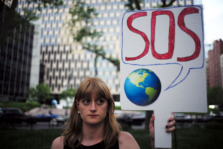 A woman displays a placard during a demonstration in New York in June 2017 to protest President Donald Trump's decision to pull out of the 195-nation Paris climate accord.