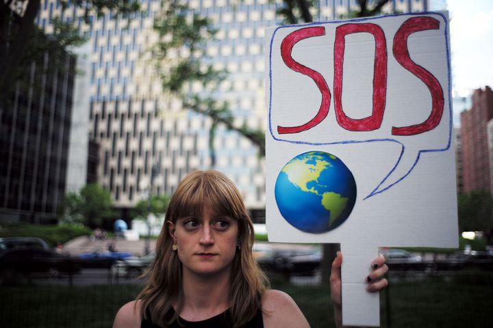 <i>Une femme brandit une pancarte pendant une manifestation &agrave; New York en juin 2017 contre la d&eacute;cision du pr&eacute;sident Donald Trump de se retirer de l&rsquo;accord de Paris sur le climat.</i>